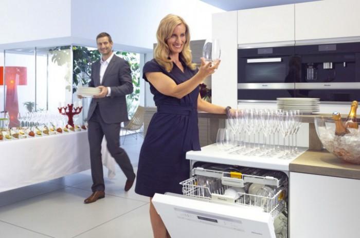 девушка достает посуду из посудомоечной машины
